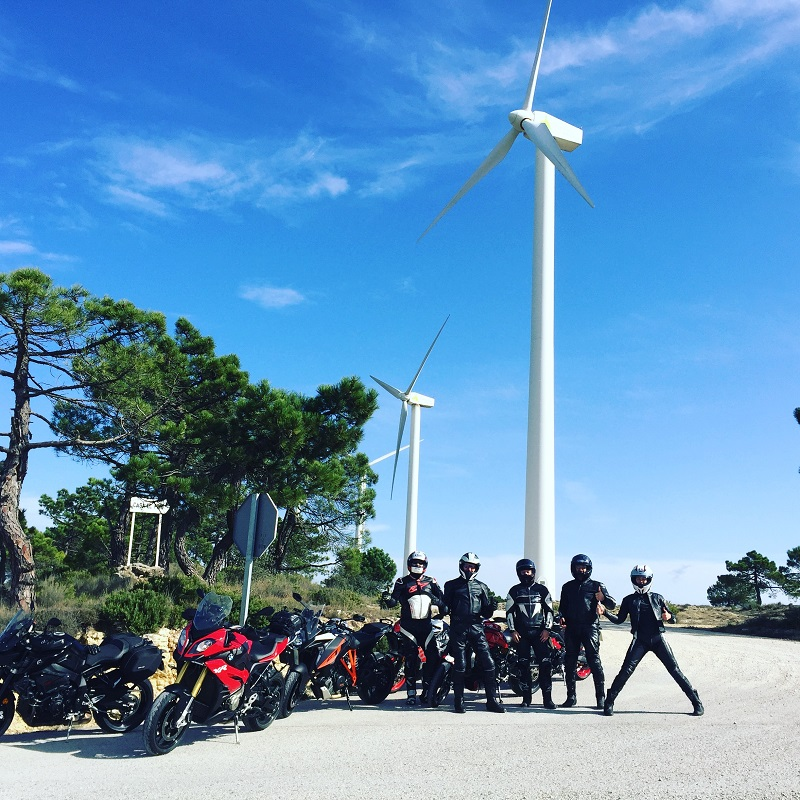 Spyder Motorcycles Tour Group for the Season Finale in Spain, a group of bikes and riders posed under wind turbines.
