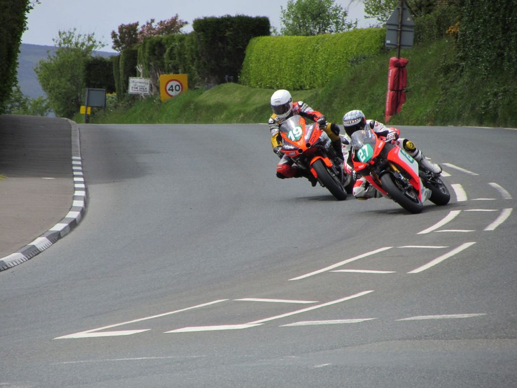 Two Isle of Man TT riders banking round a corner