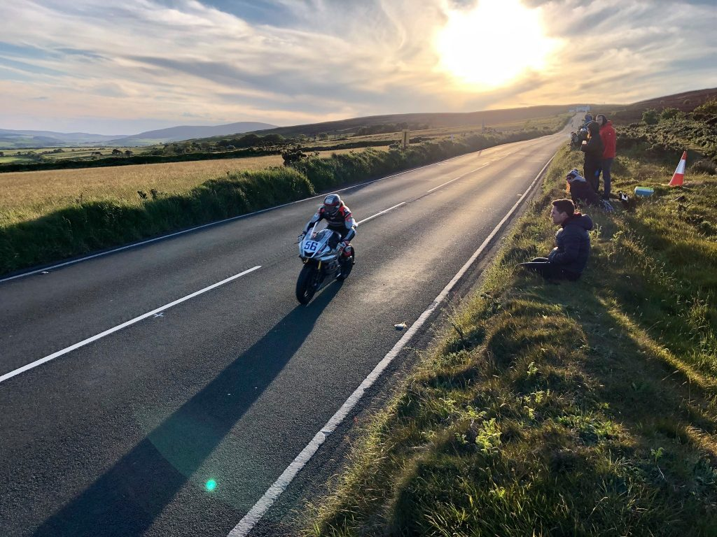 View of an Isle of Man TT rider blasting along the road with the sun setting behind